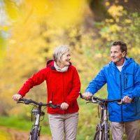 Active seniors having walk with bike on community trail enjoying autumn nature.